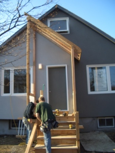 the framework for a new porch being added to the front of a newly renovated home exterior