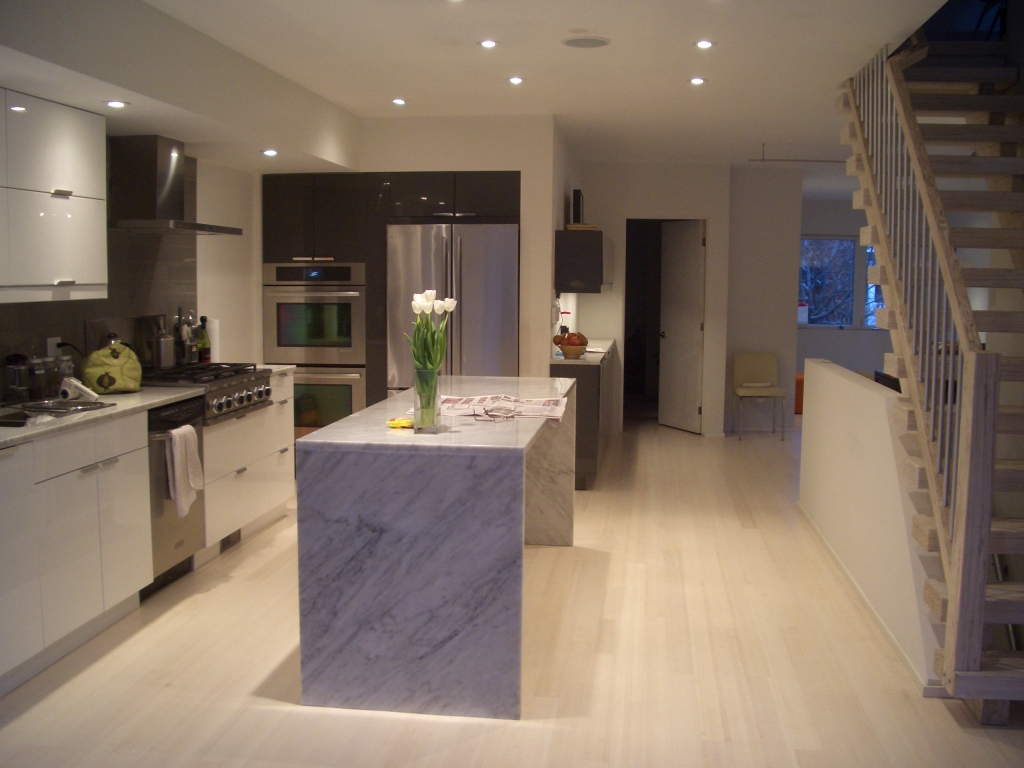 Modern home renovation, kitchen with rectangular island of marble. Beautiful pale wood floors
