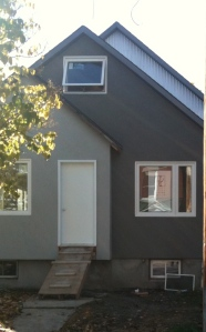 New contemporary look to home exterior with rich greys and siding removed replaced with textured flat surfaces.