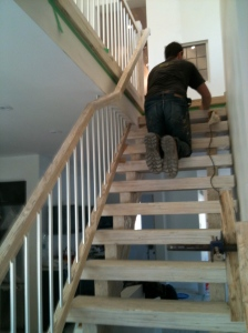 staircase being put together with nail gun. Railing has been added.